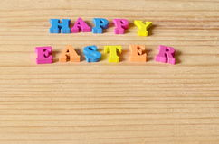 Glücklicher Ostern-Hintergrund Gruß mit bunten Buchstaben auf einem hölzernen Hintergrund Lizenzfreie Stockfotografie