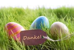Glücklicher Ostern-Hintergrund mit bunten Eiern und Aufkleber mit deutschem Text Danke Stockfotos