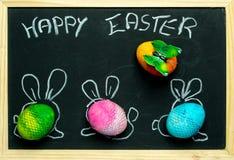 Glücklicher Ostern-Kartenhintergrund - drei bunt, Pastell-Ostereier mit den gemalten Hasenohren vor dem hintergrund einer Tafel lizenzfreies stockbild