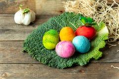 Glücklicher Ostern-Kartenhintergrund - Pastell, handgemalte, süße, bunte Ostereier auf einem einfachen, rustikalen Holztisch lizenzfreie stockfotos