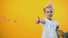 Glücklicher Ostern-Text, nettes Kind mit Eikorb in den Häschenohren, die sich Daumen zeigen stock footage