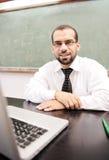 Glücklicher positiver Lehrer mit Laptop Lizenzfreie Stockbilder