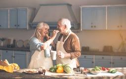 Glücklicher reifer Ehemann und Frau, die geschmackvolle Brötchen mit Tee isst lizenzfreies stockfoto
