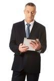 Glücklicher reifer Mann, der digitale Tablette verwendet Stockbild