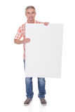 Glücklicher reifer Mann, der leeres Plakat hält Lizenzfreie Stockbilder
