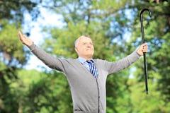 Glücklicher reifer Mann mit dem Stock, der seine Arme verbreitet Lizenzfreie Stockfotografie