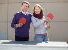 Glücklicher reifer Mann und eine Frau, die Tischtennis spielt lizenzfreie stockfotos