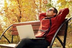 Glücklicher reifer Mann unter Verwendung des Laptops beim Sitzen auf Zaun gegen See Jung es Spezialist eine Pause von der Arbeit  lizenzfreie stockbilder