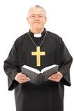 Glücklicher reifer Priester, der eine heilige Bibel hält Stockfoto