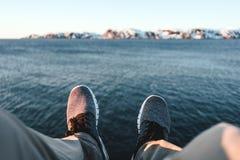 Glücklicher Reisender, der auf Felsen und Blicken auf Beinen und Schuhen sitzt Pov-Ansicht über Füße auf Hintergrund von Ozean un Lizenzfreie Stockbilder