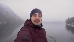 Glücklicher Reisendmann, der selfie am Ritsa See in Abchasien im Winter nimmt stock video