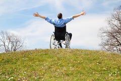 Glücklicher Rollstuhlfahrer auf einem grünen Hügel Stockfotografie