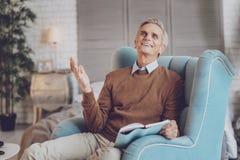 Glücklicher Ruhestand, der in seinem Raum sitzt lizenzfreie stockbilder