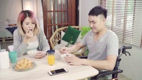 Glücklicher süßer asiatischer Paarmann in einem Rollstuhl, der, Getreide in der Milch, Brot frühstückt und Orangensaft trinkt stock footage
