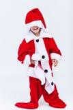 Glücklicher Sankt-Helfer, der auf sehr großem Weihnachtskostüm versucht stockfoto