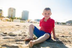 Glücklicher schöner lächelnder kleiner Junge, der am Sandstrand, Kamera betrachtend sitzt Stockfoto