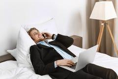 Glücklicher schöner Manager mit stilvollem Haarschnitt und Bart, der auf Bett im Hotelzimmer liegt, am Telefon spricht und seins  Lizenzfreies Stockbild