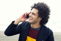 Glücklicher schöner Mann, der am Telefon spricht Stockbilder