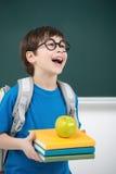 Glücklicher Schüler. Glücklicher kleiner Schüler, der den Buchstapel a hält Stockbild