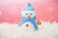 Glücklicher Schneemann, der im blauen Winterweihnachtsschneehintergrund steht Lizenzfreie Stockfotografie