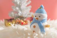 Glücklicher Schneemann, der im blauen Winterweihnachtsschneehintergrund steht Lizenzfreie Stockfotos