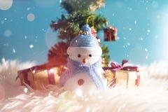 Glücklicher Schneemann, der im blauen Winterweihnachtsschneehintergrund steht Grußkarte der frohen Weihnachten und des guten Ruts Stockfotografie