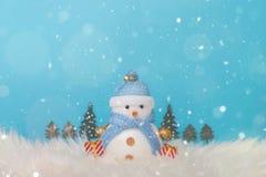 Glücklicher Schneemann, der im blauen Winterweihnachtsschneehintergrund steht Weihnachtslandschaft mit Geschenken und Schnee Froh Stockfotografie