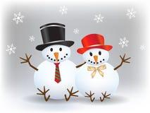 Glücklicher Schneemann mit seiner Schneedame mit Schneeflocken auf Weihnachten Lizenzfreies Stockfoto