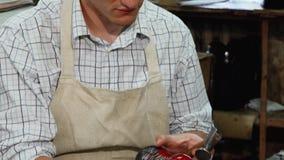Glücklicher Schuster, der zur Kamera, bei der Herstellung von Schuhen lächelt stock video
