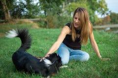 Glücklicher Schwarzweiss-Hund, der im Hinterhof, Betrieb spielt und mit seinem Eigentümer während des Sommertages springt stockfoto