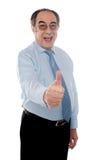 Glücklicher Senior Manager, der mit Thumbs-upgeste aufwirft stockfoto