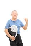 Glücklicher Senior mit der gegriffenen Faust, die eine Gewichtsskala hält Stockfoto