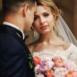 Glücklicher sinnlicher hübscher Bräutigam und blonde schöne Braut im Weiß Stockbild