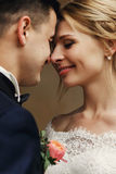 Glücklicher sinnlicher hübscher Bräutigam und blonde schöne Braut im Weiß Lizenzfreies Stockbild