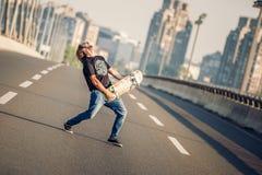 Glücklicher Skateboardfahrer auf der Brücke, die Gitarre auf seiner Rochenboa spielt Lizenzfreie Stockbilder