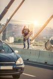 Glücklicher Skateboardfahrer auf der Brücke, die Gitarre auf seiner Rochenboa spielt Stockfotografie