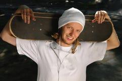 Glücklicher Skateboardfahrer, der auf Kamera aufwirft stockfotografie