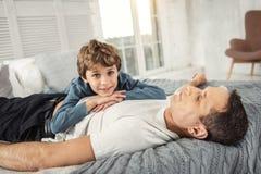 Glücklicher Sohn und Vati, die auf Bett sich entspannt Lizenzfreie Stockfotos