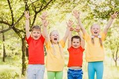 Glücklicher Spaß scherzt in den bunten T-Shirts draußen, die Freude an den Kindern stockfotos