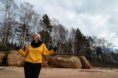 Glücklicher Sport- und Modeliebhaberenthusiast, der auf einem Strand trägt helle gelbe Strickjacke und schwarze Handschuhe und  stockbild