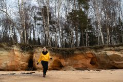 Glücklicher Sport- und Modeliebhaberenthusiast, der auf einem Strand trägt helle gelbe Strickjacke und schwarze Handschuhe und  lizenzfreies stockfoto