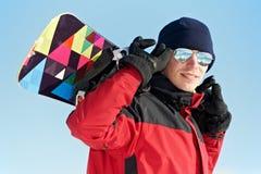 Glücklicher Sportler mit Snowboard Stockfotos