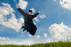 Glücklicher springender Absolvent draußen Stockfotografie