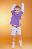 Glücklicher springender netter Junge im violetten T-Shirt Stockfoto