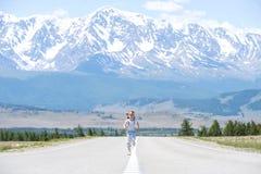 Glücklicher springender Tourist des kleinen Mädchens auf der leeren Straße des schönen Gebirgssommers Genießen des Reisens Schnee stockfoto