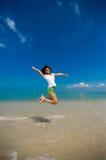 Glücklicher Sprung am Strand stockbild