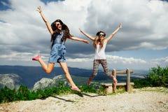 Glücklicher Sprung von zwei Mädchen in den Bergen Stockfotografie