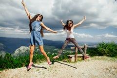 Glücklicher Sprung von zwei Mädchen in den Bergen Lizenzfreies Stockfoto