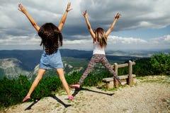 Glücklicher Sprung von zwei Mädchen in den Bergen Lizenzfreie Stockfotos