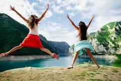 Glücklicher Sprung von zwei Mädchen in den Bergen Stockbilder
